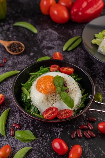 Roer boerenkool en gebakken ei in een pan. Gratis Foto