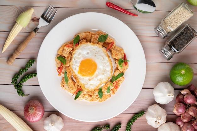 Roer de gebakken chili paste kip met rijst gebakken eieren in witte plaat op houten tafel. Gratis Foto