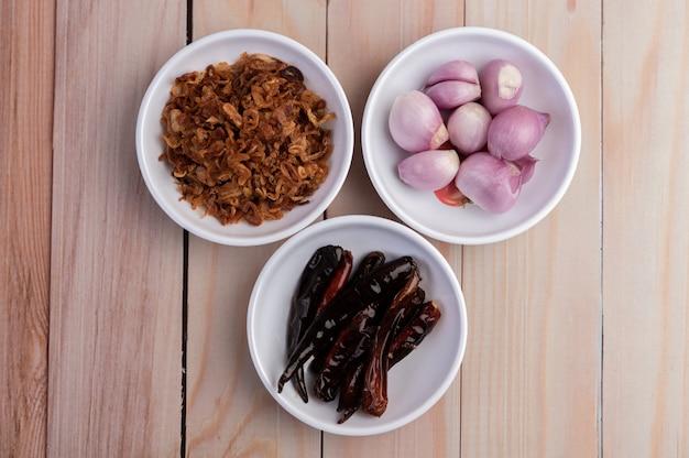 Roerbak uien, gedroogde pepers en rode uien in een witte plaat op een houten vloer. Gratis Foto