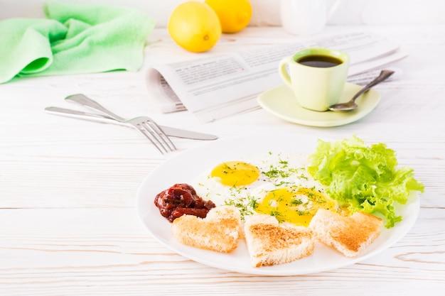 Roerei, gebakken brood, ketchup en slabladeren op een bord, kopje koffie en krant op de tafel. Premium Foto