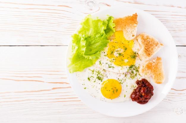 Roerei, gebakken brood, ketchup en slabladeren op een bord op de tafel Premium Foto