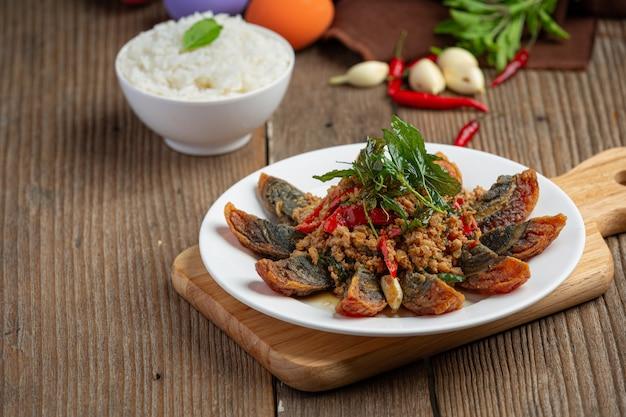 Roergebakken basilicum met pittig ei uit de eeuw geserveerd met gestoomde rijst en chili vissaus, thais eten. Gratis Foto