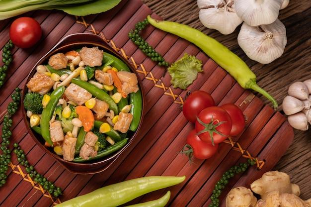 Roergebakken gemengde groenten met doperwten, wortelen, champignons, maïs, broccoli en varkensvlees Gratis Foto