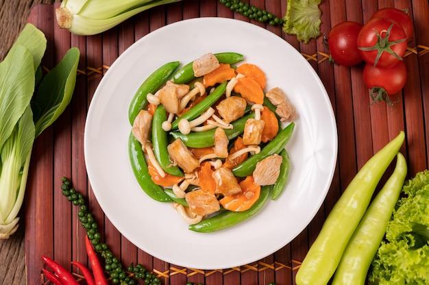 Roergebakken groene erwten met varkensvlees champignons en wortelen liggen op een witte plaat Gratis Foto