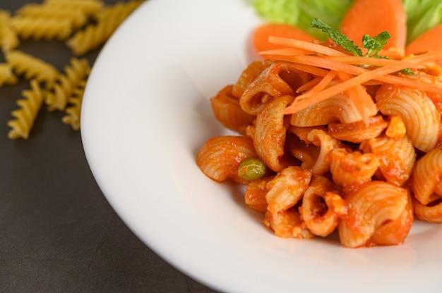 Roergebakken macaroni met tomatensaus en varkensvlees Gratis Foto