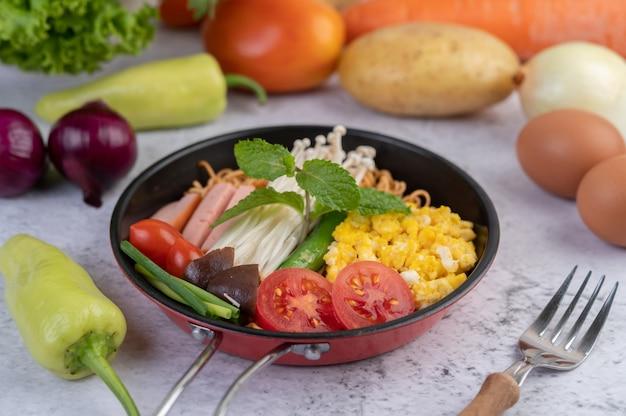 Roergebakken noedels die mais, champignons, tomaat, worst, edamame en lente-uitjes in een koekenpan combineren. Gratis Foto