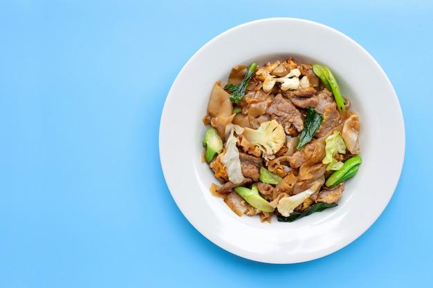 Roergebakken platte noedels en varkensvlees met sojasaus. bovenaanzicht Premium Foto