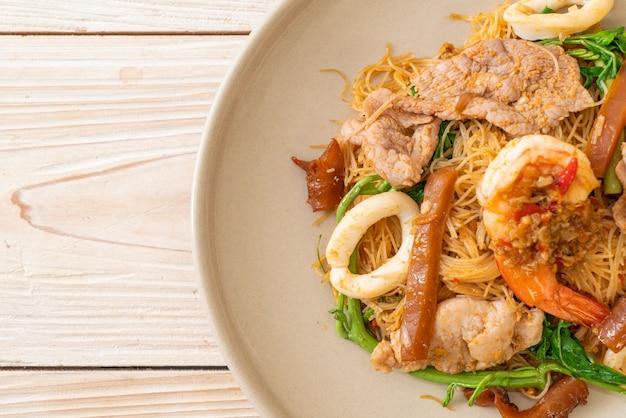 Roergebakken rijstvermicelli en watermimosa met vleesmix Premium Foto