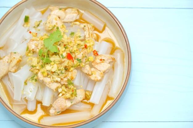 Roergebakken van shanghai-noedels met varkensvlees en zure saus op blauwe tafel Premium Foto