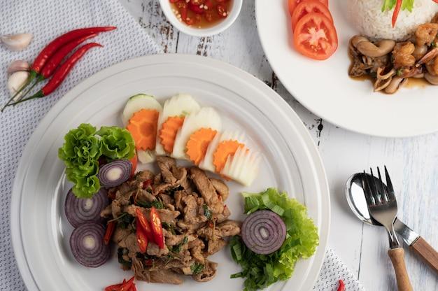 Roergebakken varkensvlees basilicum op een witte plaat met wortelen, komkommer en ui. Gratis Foto