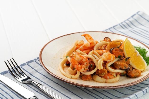 Roergebakken zeevruchten met saus op plaat met servet Premium Foto