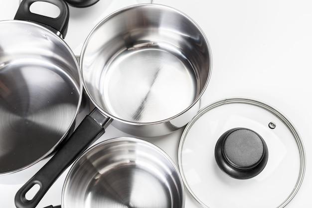 Roestvrij staalpotten en pannen op wit worden geïsoleerd dat Premium Foto