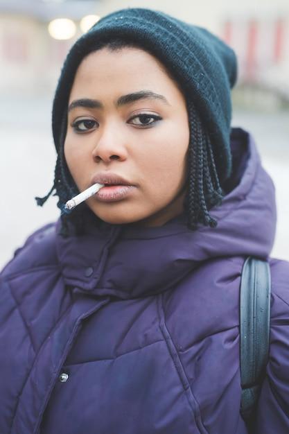 Rokende sigaret van de portret de jonge vrouw Premium Foto