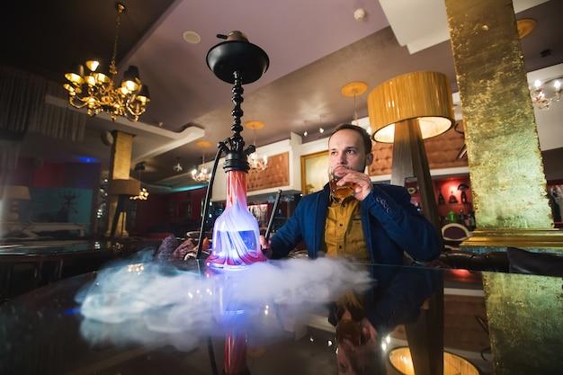 Rokende waterpijp, de mens blaast rook Premium Foto