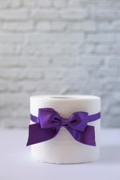 Rol wit toiletpapier gebonden met paars lint met een strik, verticale oriëntatie. wc-rol met lila strik Premium Foto