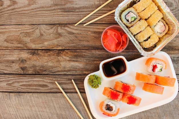 Rollen, wasabi, sojasaus, gember op tafel. bovenaanzicht. Premium Foto
