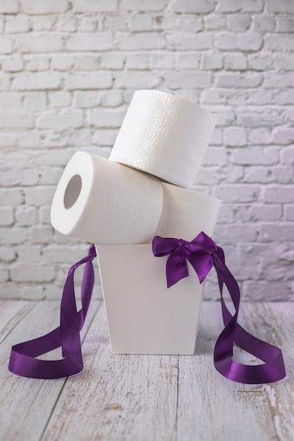 Rollen wit toiletpapier liggen in witte geschenkdoos met paarse linten en strik, verticale oriëntatie Premium Foto