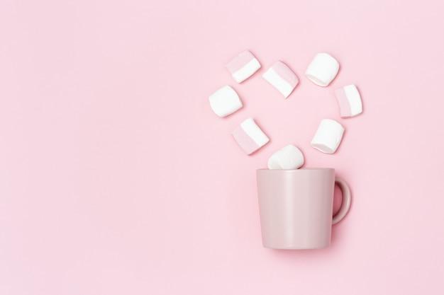 Romantiek vakantieconcept, roze mok of beker en marshmallows in vorm van hart, liefdesverklaring Premium Foto