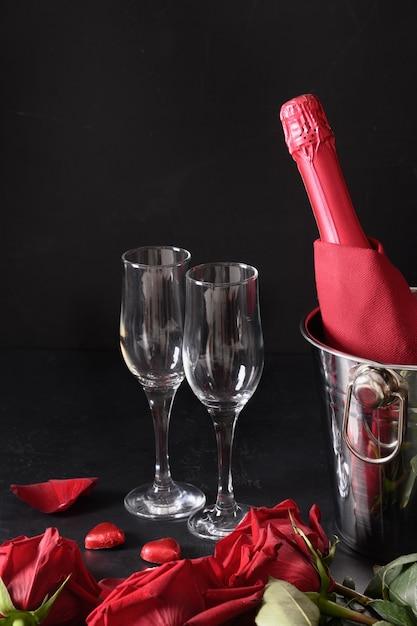 Romantisch daten met koude mousserende wijn, snoep en rode rozen op zwart. viering voor valentijnsdag. verticaal formaat. Premium Foto