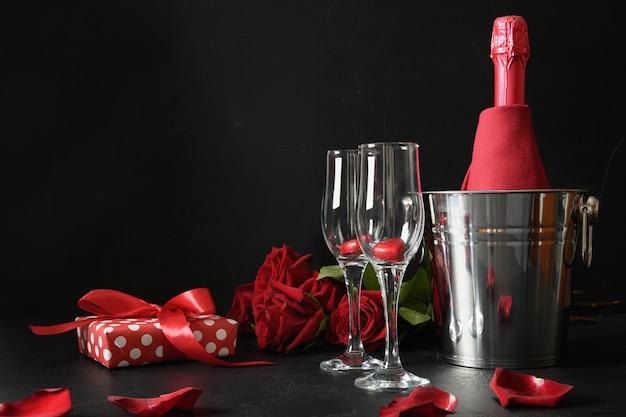 Romantisch daten met mousserende wijn, cadeau, boeket rode rozen op zwart. viering voor valentijnsdag. Premium Foto
