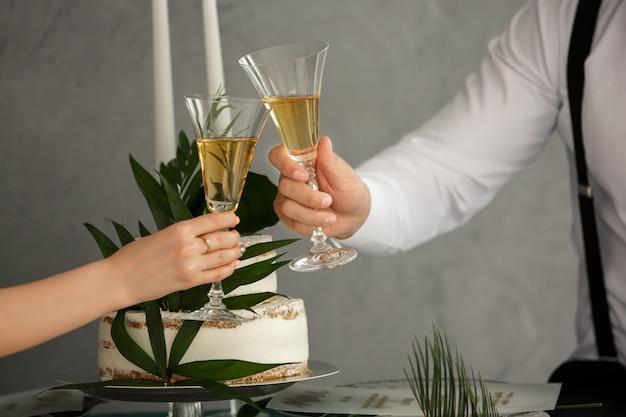 Romantisch diner of date met champagneglazen. toast en rammelt met alcoholische dranken. viering op bruiloft. huwelijk concept Premium Foto