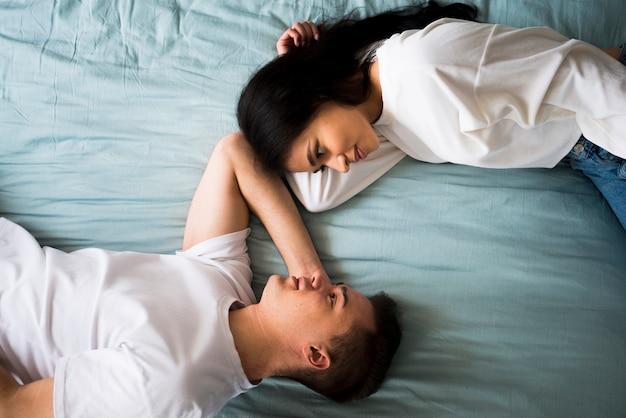 Romantisch houdend van paar die op bed liggen en ogen onderzoeken Gratis Foto