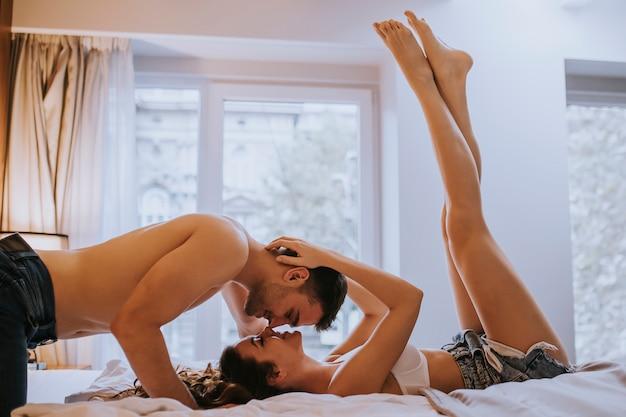 Romantisch jong paar dat op het bed met lichamen in tegenovergestelde richtingen legt terwijl het kussen Premium Foto