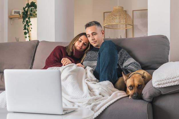Romantisch jong stel en hun hond gezellig thuis, ontspannen op de bank tijdens het kijken naar films op laptop Premium Foto