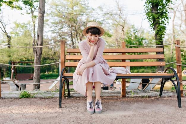 Romantisch meisje met trendy strooien hoed zittend op een bankje gezicht met hand steunen en na te denken over iets goeds Gratis Foto