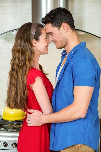 Romantisch paar die zich van aangezicht tot aangezicht bevinden en elkaar in keuken omhelzen Premium Foto