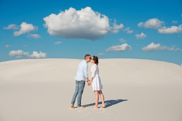 Romantisch paar in liefde kussen op het witte zand in de woestijn Premium Foto