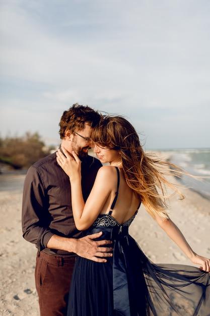Romantisch paar omhelzen op het strand van de avond in de buurt van de oceaan. elegante vrouw in blauwe jurk knuffelen haar vriendje met tederheid. Gratis Foto