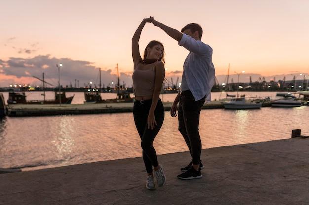 Romantisch paar uit bij zonsondergang in de haven Gratis Foto
