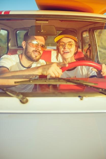 Romantisch paar zittend in de auto tijdens een road trip lachen Gratis Foto