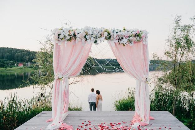 Romantisch portret van achter van bruidspaar die zich achter huwelijksboog bevinden en van schilderachtig aardlandschap in de zomerzonsondergang genieten Premium Foto
