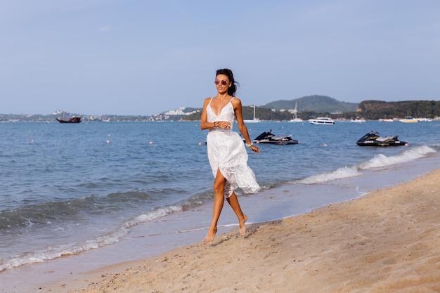 Romantisch portret van gebruinde vrouw in witte zomerjurk op tropisch strand bij zonsondergang Gratis Foto