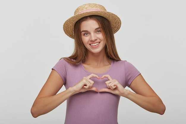 Romantisch portret van tedere charmante vrouw op een witte achtergrond. vrouw toont hartvorm gebaar met handen Gratis Foto