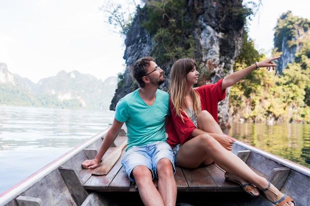 Romantisch reizend paar dat samen vakantietijd doorbrengt, zittend op een langstaartboot, de wilde natuur van het khao sok nationaal park verkennen. Gratis Foto