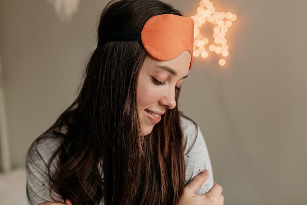 Romantisch verlegen meisje met donker haar slaapmasker dragen op het hoofd thuis rusten. 's ochtends thuis wakker worden Gratis Foto