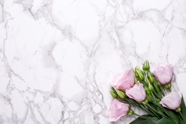 Romantische achtergrond met roze bloemen op marmeren tafel Premium Foto