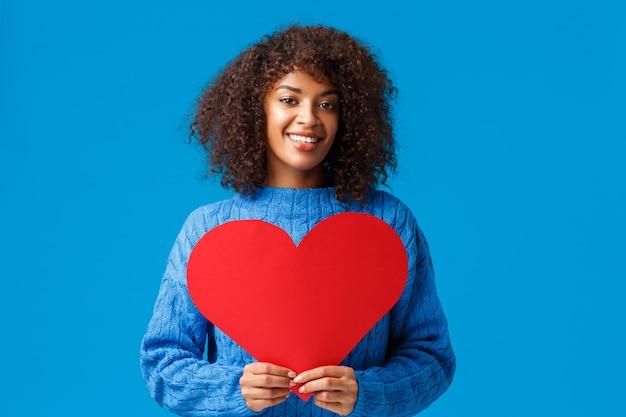 Romantische en sensuele schattige afro-amerikaanse vrouw met afro kapsel, met groot rood hartteken en glimlachend. Gratis Foto