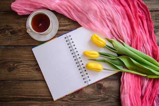 Romantische foto met kladblok, tulpen en een kopje thee op houten achtergrond Premium Foto