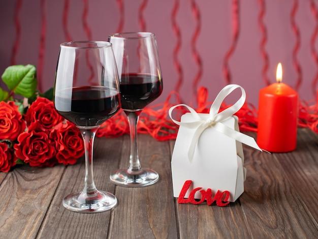 Romantische gezellige avond met wijn, bloemen, kaarsen en cadeau Premium Foto