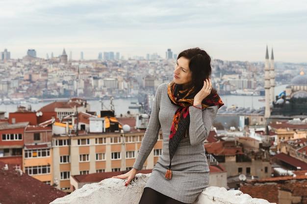 Romantische jonge vrouw geniet van een schilderachtig panoramisch uitzicht over istanbul vanaf het dak. Premium Foto