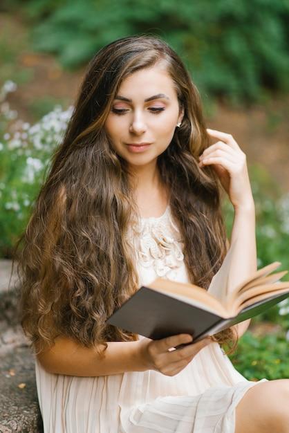 Romantische langharige jonge mooie vrouw die een boek leest Premium Foto