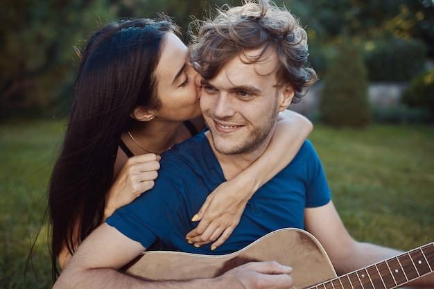 Romantische paarzitting op het gras in de tuin Gratis Foto