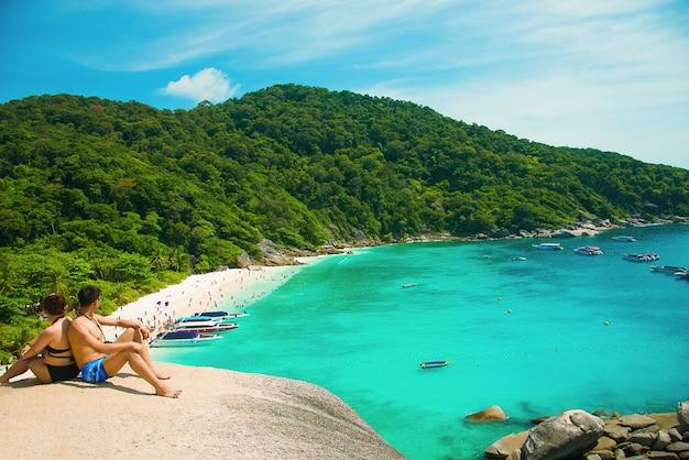 Romantische scène van de jonge zitting van het liefdepaar met het ontspannen en geluk op het strand in similan-eilanden Premium Foto