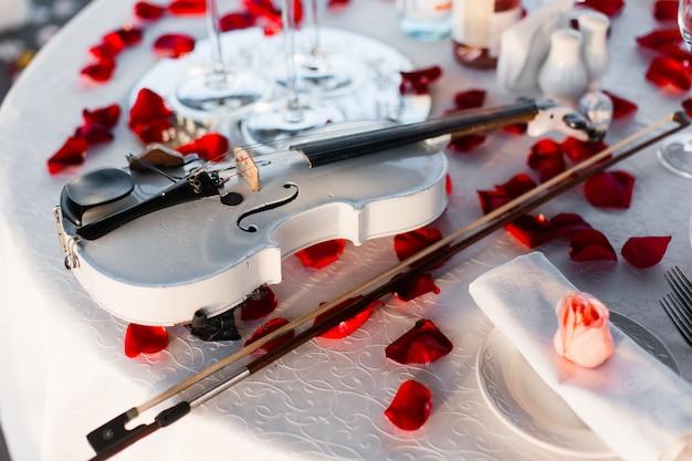 Romantische valentijn tafel instelling met wijn, servies, lege glazen, rozenblaadjes, kaarsen, viool Premium Foto
