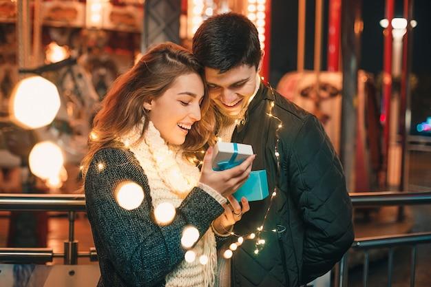 Romantische verrassing voor kerstmis, vrouw ontvangt een geschenk van haar vriend Gratis Foto