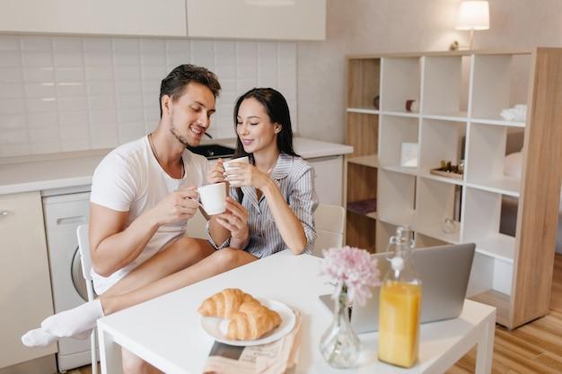 Romantische vrouw in witte sokken koelen met echtgenoot tijdens het ontbijt en genieten van croissants Gratis Foto